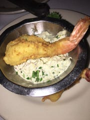 The shrimp appetizer consists of two fried shrimp served with a zesty white remoulade.