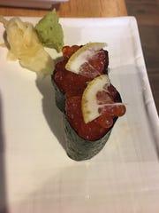 Nigiri sushi, topped with lemon.