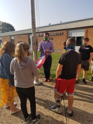 U.S. Marines Staff Sergeant Tyler Harman shows Mrs. Fix's fifth-grade class how to properly attach the American Flag to a flagpole this week.