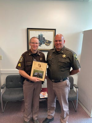 Ionia County Sheriff Charlie Noll (right) and Sgt. Dion Sower pose with a photo of a plaque dedicated to the memory of K-9 Dinar, who died in January. Sower was Dinar's K-9 handler.