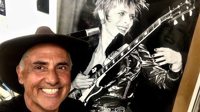 Victor Reyes, next to a poster of one of rock music's most iconic talents and a  personal musical hero.