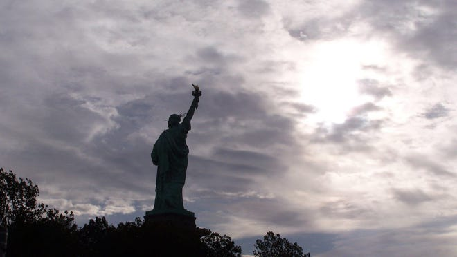 The sun starts to peek through clouds as the Statue of Liberty looks out over New York Harbor.