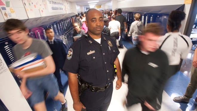 Roberto Grider, a school resource officer at the Marion C. Moore Middle-High School on Outer Loop, stands in the high school hallway between classes.30 August 2017