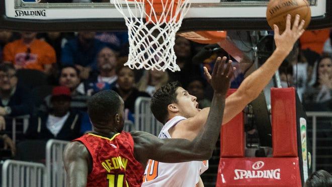 New York Knicks forward Doug McDermott, right,  shoots a reverse lay up on Atlanta Hawks center Dewayne Dedmon, left, during the first half of a NBA basketball game, Friday, Nov. 24, 2017, in Atlanta.