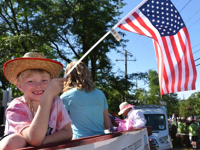 Tenyson Keyser, 7, holds an American Flag while waiting