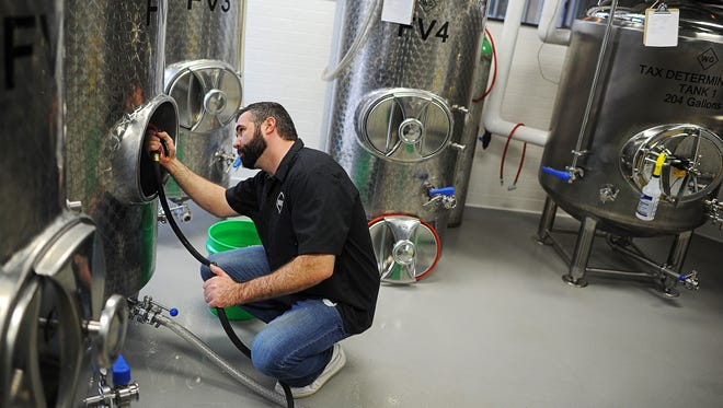 Steve Hartman, part-owner and brewer at WoodGrain Brewing Company, cleans out a fermentor Friday at WoodGrain Brewing Company in downtown Sioux Falls.