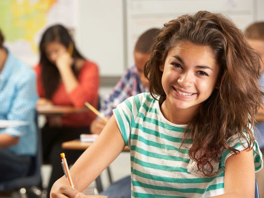 Portrait Of Female Pupil Studying At Desk In Classroom