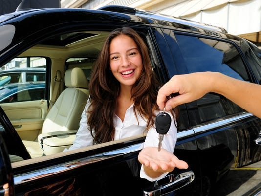 Woman sitting in new status car and receiving keys