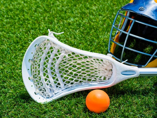 Orange ball, white Lacrosse stick and helmet on artificial turf