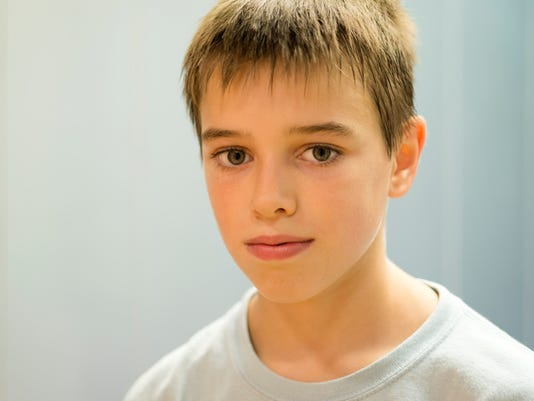 Portrait of Pensive Eleven Years Old Boy, Gray Wall, Europe