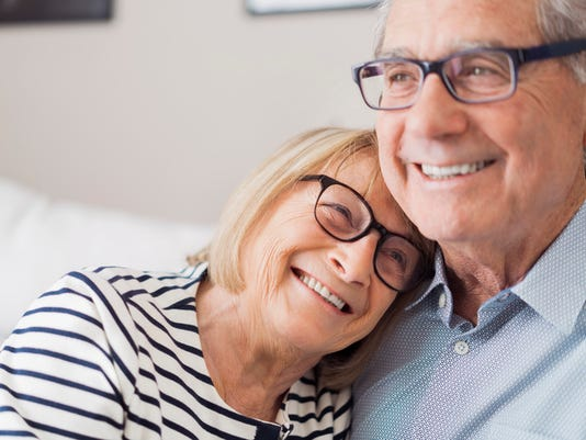 Senior woman leaning head on senior man's shoulder