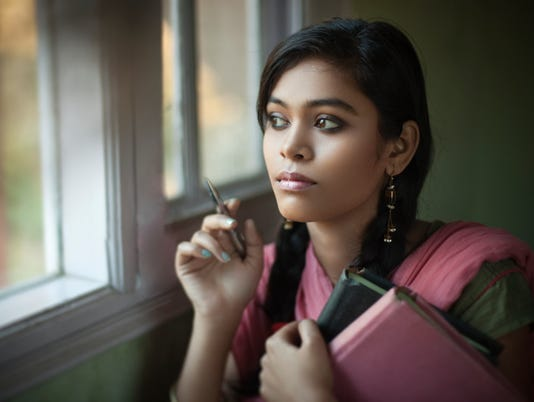 Indoor, serene Asian teenage girl student near window with books.