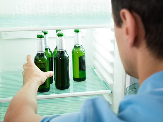 Young Man Removing Beer Bottle From Refrigerator