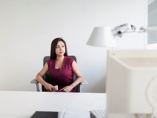 Young Indian woman sitting in private office space