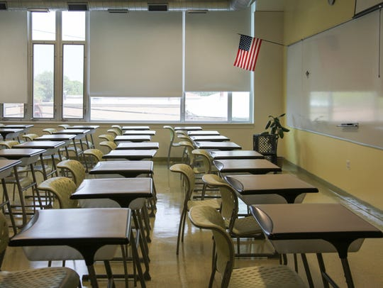 An empty classroom with rows of desks