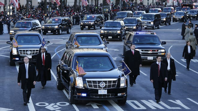 Secret Service agents walk along President Obama's car during the inaugural parade earlier this year.