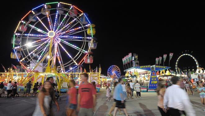Crowds of people play games and check out the amusement rides on the midway at the annual Delaware State Fair last year.