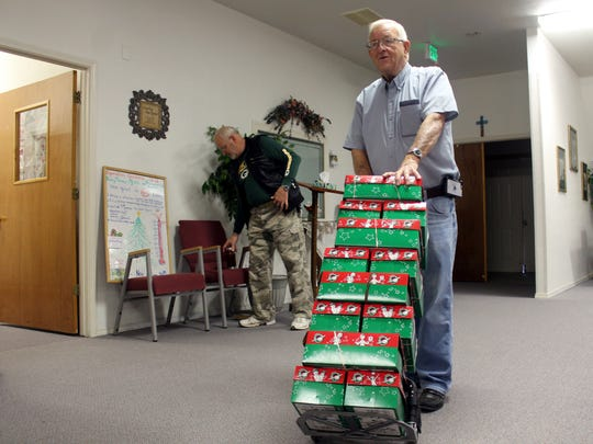A volunteer brings in donated shoeboxes into Grace Baptist Church on Saturday.
