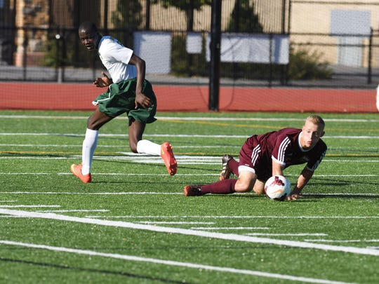 After a collision, Arlington's Max Giancarlo, right, notices he still has possession of the ball, while FDR's Bethuel Yebouet, left, looks back in confusion.