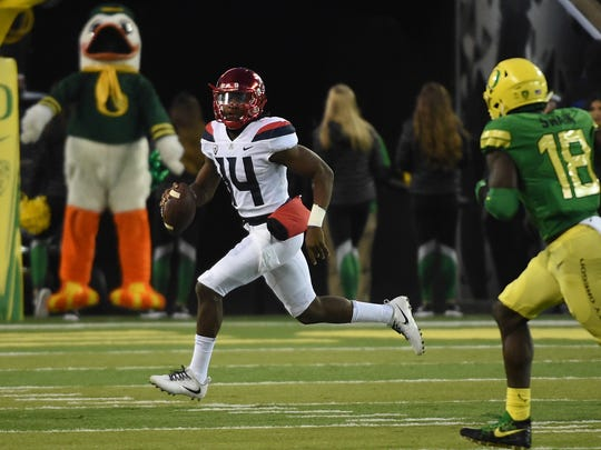 Arizona quarterback is chased out of the pocket by