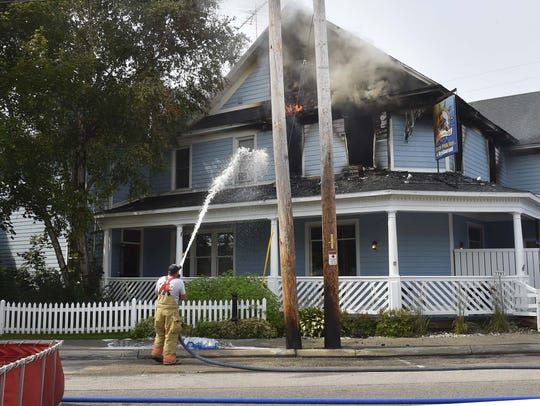 A firefighter douses a hot spot in the aftermath of