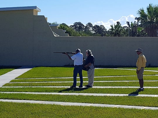 Indian River County Commission Chairman Peter O'Bryan (in white shirt) takes aim at a clay target Dec. 1, 2017, while receiving instruction from former Team USA medal-winner Steve Fischer at the Indian River County Public Shooting Range Trap and Skeet facility in Sebastian.