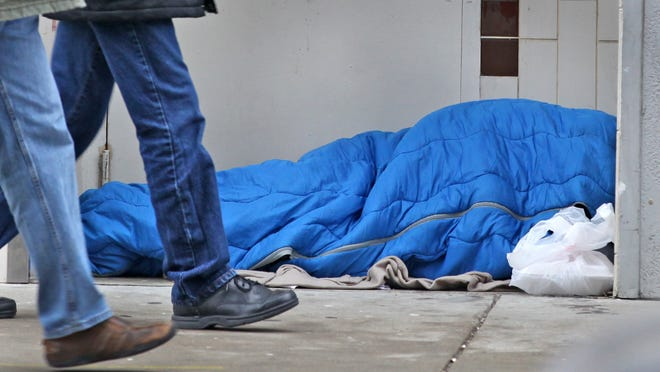 People walk past a homeless person sleeping inside a doorway on Pennsylvania St., Thursday, January 29, 2015.
