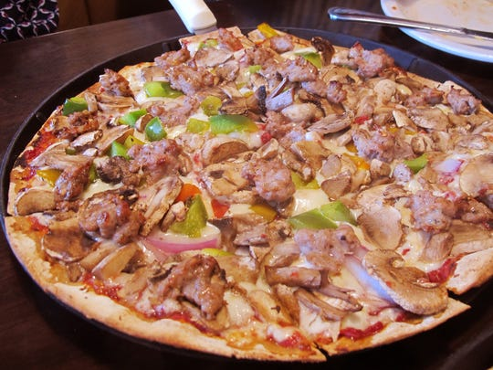 The Henning Family Heirloom thin-crust pizza at Henning's Chicago Kitchen, 2360 Pine Ridge Road, Naples, features house-made Italian sausage, roasted peppers, mushrooms and onion.