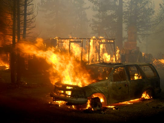 A home and a car burn near South Lake Tahoe during the Angora Fire in June 2007