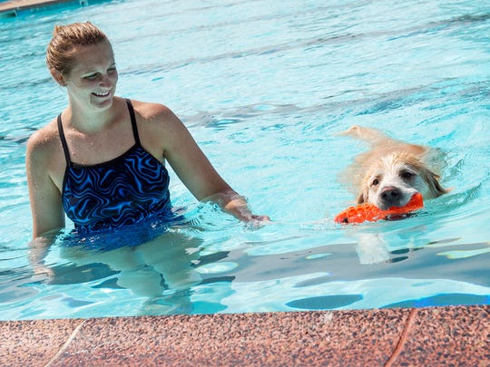 Betsy Wilson plays catch with her dog, Franklin, a yellow lab, during Puppy Paddle on Saturday. Sept. 10, 2016. Puppy Paddle is the only day you can bring your dog to the pool and the ending of the pool season.