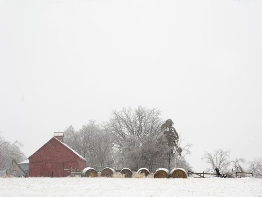 Snow falls on a farm north of Indianola during a December