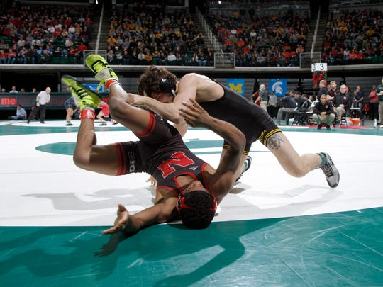 Iowa's Vince Turk, right, rolls Nebraska's Chad Red in their 141-pound match, Saturday, March 3, 2018, in East Lansing, Mich.
