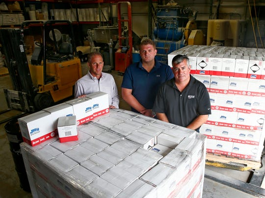 American Oil & Supply International's President Chuck Decker (right) is shown with Specialty Products Manager John Dunn (center) and Dan Managlia from Technical Services speaks Wednesday, September 20, 2017, in their Eatontown warehouse.  The company's 'Jack of All Sprays' recently won a competition to get its product sold at Walmart.