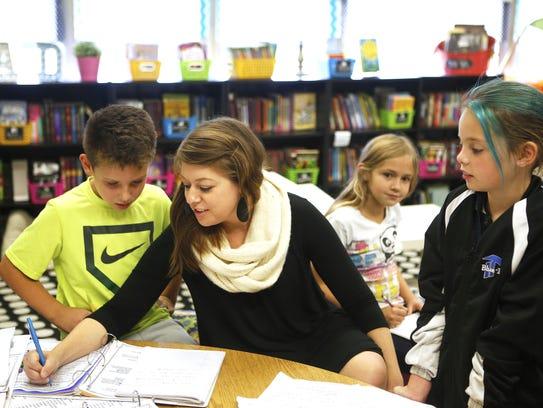 Fifth grade teacher Stacey Riedmiller works with Aiden