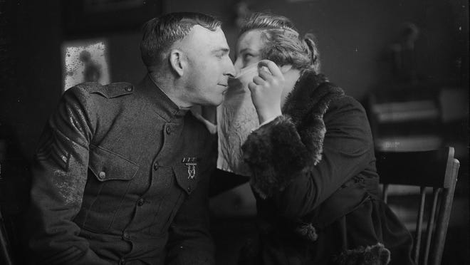This October 1918 photo from the Rochester Herald shows a couple demonstrating the proper way to kiss during the influenza epidemic — through a handkerchief.