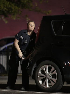 A police officer looks up while standing behind a vehicle, as police responded to shots being fired during a protest over recent fatal shootings by police in Louisiana and Minnesota, Thursday, July 7, 2016, in Dallas. Snipers opened fire on police officers during protests; several officers were killed, police said. (Maria R. Olivas/The Dallas Morning News via AP)