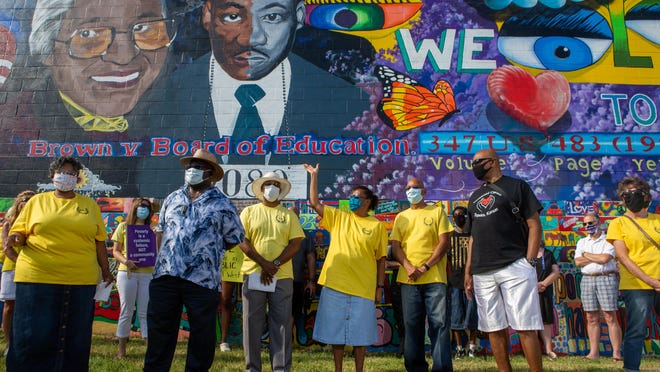 """A woman leads members of Topeka JUMP in song at the beginning of a rally Monday in front of the Brown v. Board of Education mural. """"Demanding justice, we shall not be moved,"""" they sang."""