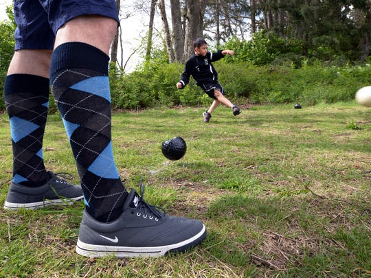 Luke Roque boots a soccer ball from the tee box during a round of Footgolf at Meadow Park Golf Course, in Tocoma, Wash.