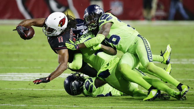 Arizona Cardinals' Larry Fitzgerald battles for an extra yard as he is tackled by Seattle Seahawks Bradley McDougald and Shaquill Griffin in the second half on Nov. 9, 2017 at University of Phoenix Stadium in Glendale, Ariz.