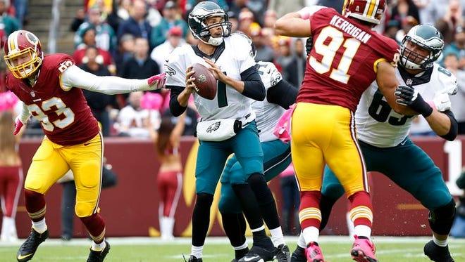 Eagles quarterback Sam Bradford looks downfield while trying to avoid Washington's pass rushers.