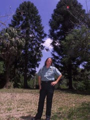 Jeanne Parks, park manager at the Koreshan State Historic Site stands in front of two giant Monkey Puzzle trees at the Estero park in 2000