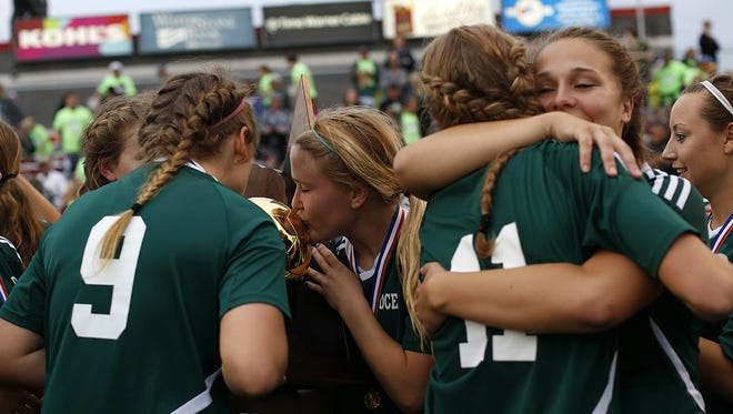 D.C. Everest players celebrate with the championship trophy after the Evergreens defeated Kettle Moraine in overtime to win the Division 1 championship game in the WIAA state girls soccer tournament at Uihlein Soccer Park in Milwaukee last June.
