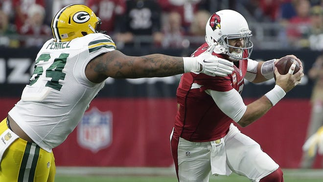 Packers defensive end Mike Pennel, suspended the first four games this season for violating the league's substance abuse policy, tries to grab Cardinals quarterback Carson Palmer last season at University of Phoenix Stadium.