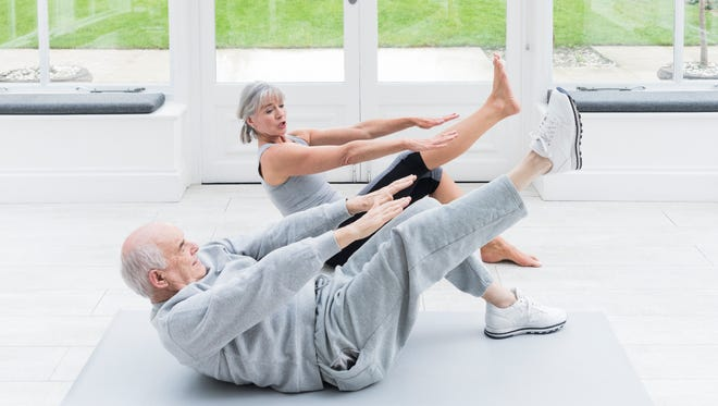 Senior man leaning back on floor with leg raised, reaching forward with arm to stretch. Using core stability strength muscles to keep fit and active. Senior female personal trainer helping man do yoga pilates.