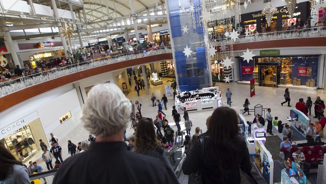 The escalators and main lobby area of the Arrowhead Towne Center are packed with people as holiday season shopping enters full swing in Glendale, AZ on Dec. 14, 2014.