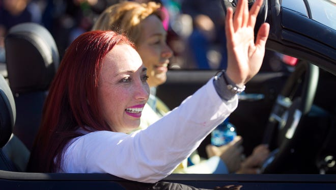 Amy Van Dyken-Roue, the Grand Marshal of the Fiesta Bowl Parade, waves to the crowd during the Fiesta Bowl Parade in Phoenix on Saturday, December 27, 2014.