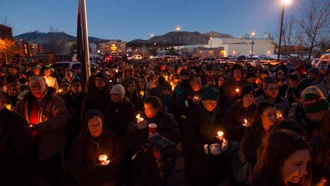 Hundreds gather and listen during a candlelight vigil for fallen officer Tyler Stewart at the Flagstaff Police Department a day after he was shot and killed in Flagstaff, Ariz.on Dec. 28, 2014.
