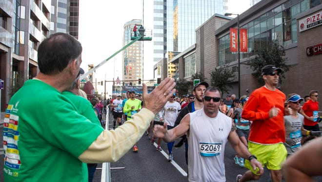 Spectators high-five runners at CityScape on Central Avenue and Washington Street in downtown Phoenix during the P.F. Chang's Rock 'n' Roll Marathon on Sunday, Jan. 18, 2015.