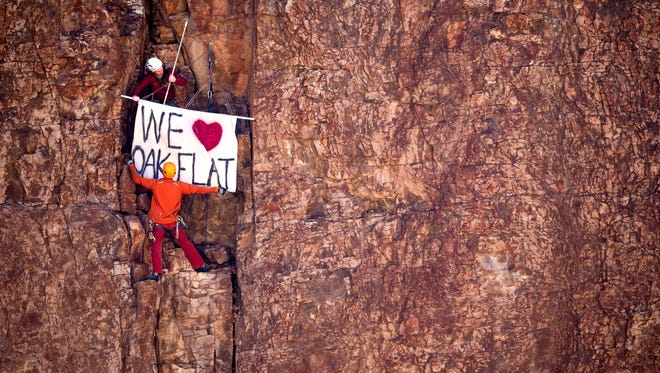 Rock climbers Aaron Collins, top, and Manuel Rangel place a banner on the middle of a cliff face near Oak Flats outside Superior on Feb. 4, 2015.