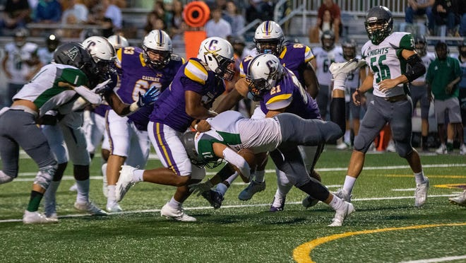 Calvary defensive players Casey Ricks (21) and Jordan Davis (62) stop Frederica Academy running back Kyle Perez (21) for a loss on Friday night at Calvary Day School. Calvary won 27-7.
